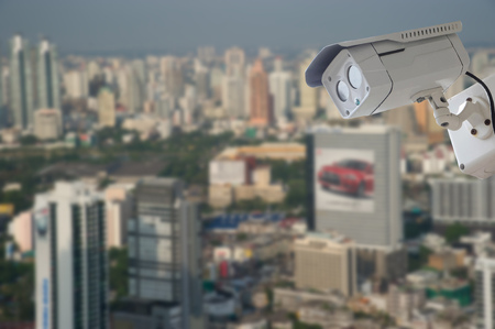 nightvision: cctv camera with modern building blur background
