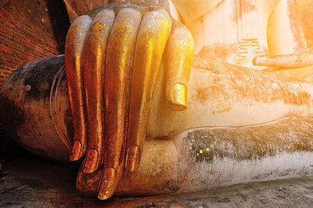 chums: Vintage style. gold leaf offerings on slender fingers of wat si chums iconic big buddha statue in sukhothai historic park northern thailand Stock Photo
