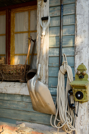 Retro telephone, shovel and rop hang on vintage wall