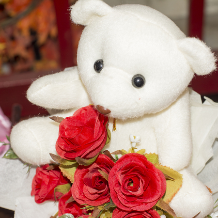 ou: teddy bear is sitting on top of the flowers (the bear doesn´t have copyright ou trademark)
