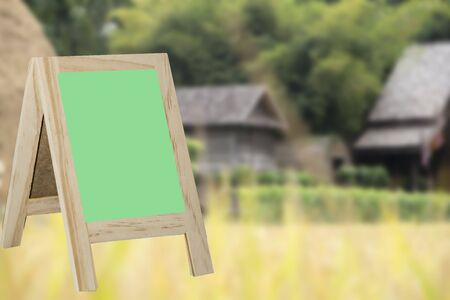 greenboard: greenboard on a blurred background green rice paddy field hut