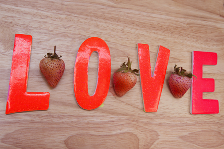 strawberrys: The word love on the wooden floor and Strawberrys background with copy space