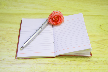 note book: Remember him with a pen, note book with flowers blurred. Stock Photo