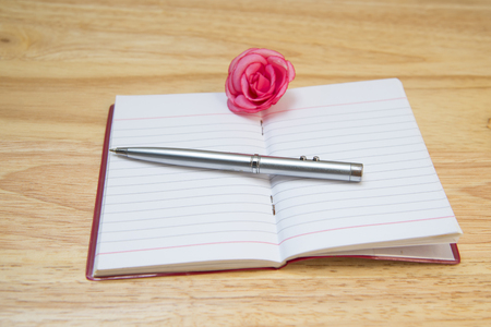 mentioned: Note the pen blurred flowers on a wooden background texture. Stock Photo