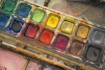 paintbox: Closeup of messy, used water-color paint-box and paint brush.
