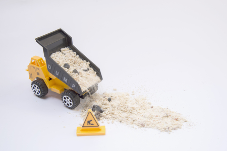 machinery space: Yellow toy truck pouring sand onto a white background Stock Photo