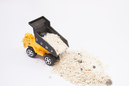 dumping: Toy truck pouring sand Background with copy space Stock Photo