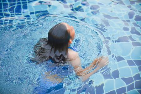 フォーカスの子供の人魚のお姉さんとプールで水泳をぼかし 写真素材