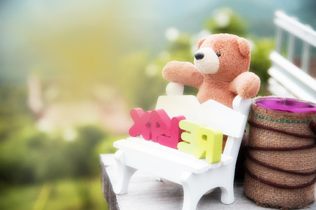 plaything: Toy bears sitting on a chair in the background scenery blurred.