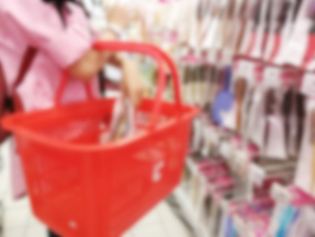 Blurry woman carrying a basket while shopping for groceries in a supermarket Stock Photo