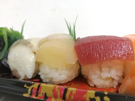 The typical sushi rice is oval shaped rice and then topped with sliced fish or seafood. 版權商用圖片