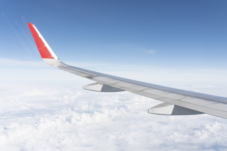 The plane wings are in the atmosphere of beautiful clouds Stock Photo - 117117823