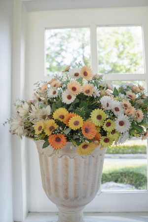 Artificial flowers in a stretcher placed on a window background. Stock Photo