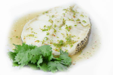 Poisson des neiges cuit à la vapeur, sauce épicée sur fond blanc
