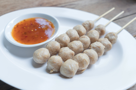Pork meatballs with dipping sauce in a white dish Imagens