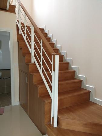 Eleganckie i drewniane schody w domu na abstrakcyjnym tle