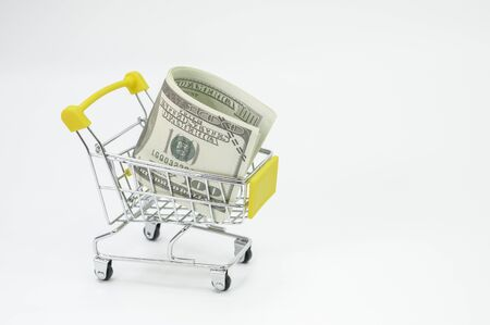Small metal cart in a white background with foreign currency