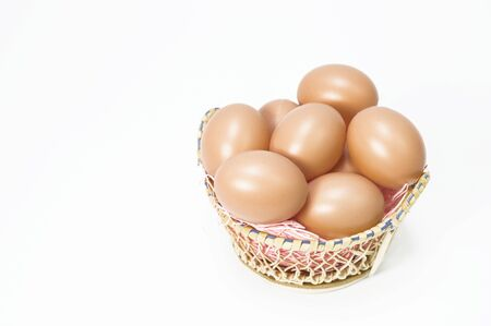 Many eggs are in a basket on a white background.