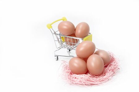 Small metal cart with many eggs on a white background 写真素材