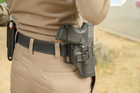 Close up of Thailand's police pistol, Policeman's equipment belt holding his weapon,