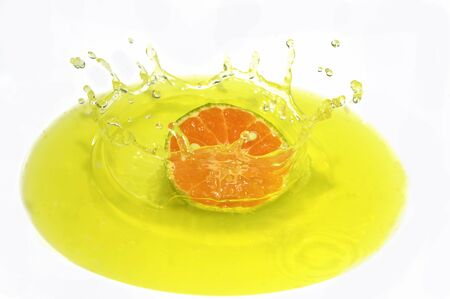 Cut oranges on the yellow background along with water droplets
