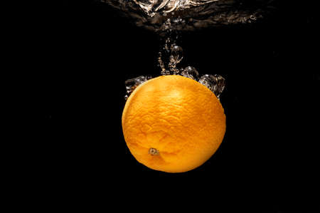 Oranges falling into water splashing on black background and good for health.
