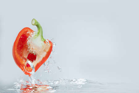 Sliced bell pepper splashes into the water. food ingredient concept