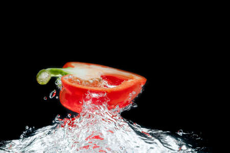 Splattered colored bell peppers splashed on a black background with a cut-out background.