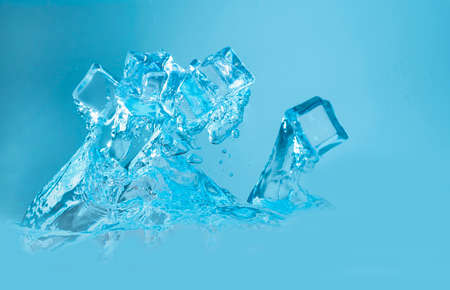 Concept of ice cubes with splashing water on blue background.