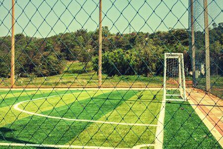 pasto sintetico: Artificial turf football field with vintage color filter and sunlight Foto de archivo