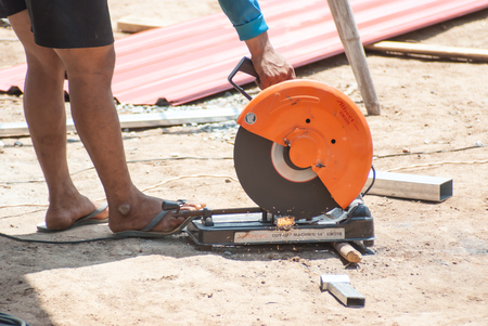 forger: PHITSANULOK - MAY 14: The smith are cutting steel with electric saw. on May 14, 2016 in Phitsanulok, Thailand.