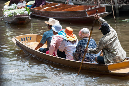 laden: RATCHABURI, THAILAND-SEPTEMBER 28: Damnoen Saduak Floating Market on September 28,2016 in Thailand. Having many small boats laden with Souvenir shop, colourful fruits, vegetables and Thai cuisine. Editorial