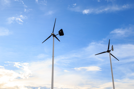 against: Wind turbine against blue sky - clean energy. Stock Photo