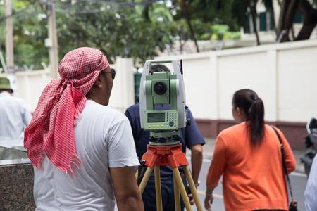teodolito: Un trabajador agrimensor trabajando con equipos de tránsito teodolito en la construcción de carreteras