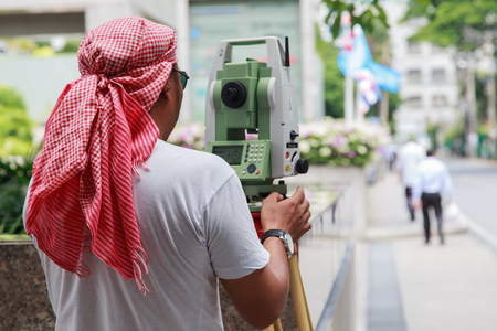 exact position: One surveyor worker working with theodolite transit equipment at road construction