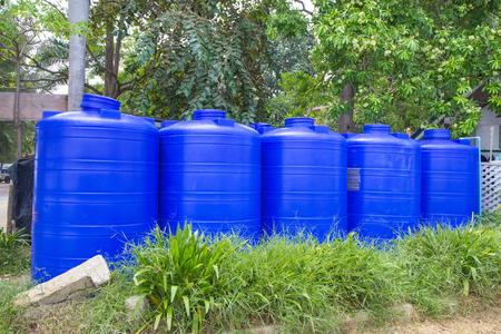 Blue plastic water tank on grass