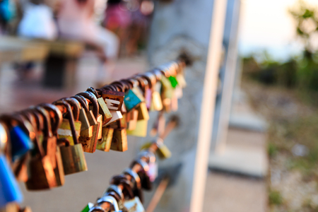 Close focus on a big lock and others blurred hang on sling at the top of Noen-nangphaya view point, Chanthaburi, Thailand. People come to hang the lock represent forever love.