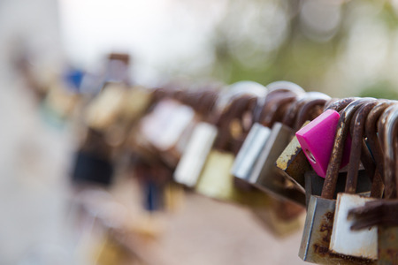 Close focus on a big lock and others blurred hang on sling at the top of Noen-nangphaya view point, Chanthaburi, Thailand. People to hang the lock represent forever love. Standard-Bild