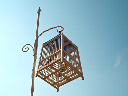 Bird cage hanging on a pole  Stock Photo