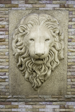 carving: a head of a lion on a wall  Stock Photo
