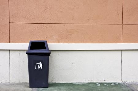 trash can: trash and wall