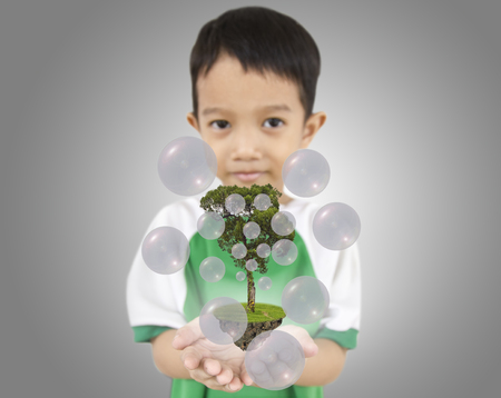 oxigen: young boy holding  a tree for the earth