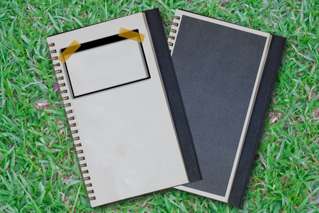 Note book on grass green background photo