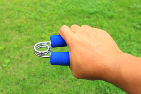 hand grip: background of hand grip exercise equipment on the right hand for physiotherapy Stock Photo