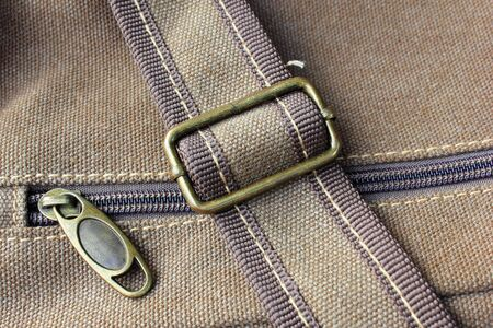 strap on: closeup background of brown haversack zipper with strap