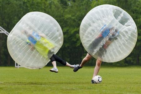 사람: Bubble football in funny moment. Concept: Fun, Sport Flying 스톡 콘텐츠