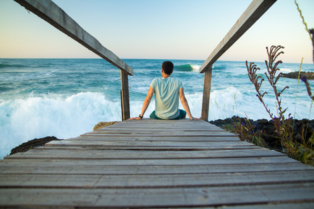 MAN SITTING ON A WOODEN BRIDGE FACING THE SEA