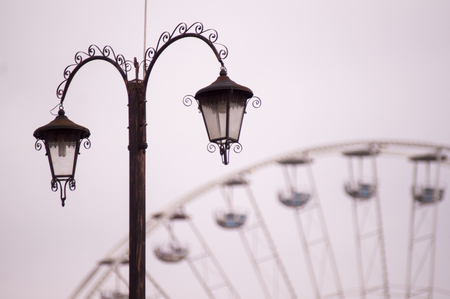 Old fashioned street lamp with ferris wheel in background