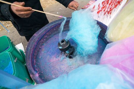 Hand rolling cotton candy in candy floss machine. Candyfloss making Imagens