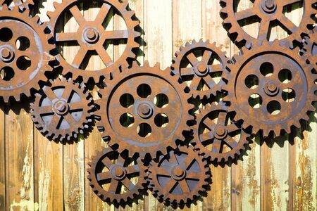 GIANT OLD AND RUSTY COGWHEELS ON THE WALL Фото со стока - 129925104